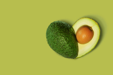 Avocado Isolated on Green background in shape of Heart. Love Symbol or Fresh Organic Fruit for Healthy Lifestyle Concept