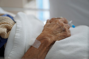 Closeup hand of sick elderly patient lying on the bed in hospital Wall mural