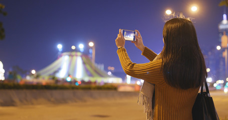 Woman taking photo on cellphone in the city at night