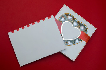 Beautiful mockup for Valentines day. Romantic box of sweets and modern note book on the red background.