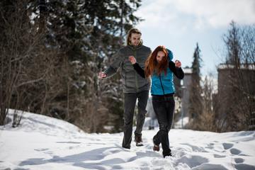 Couple having fun as they run on the snow
