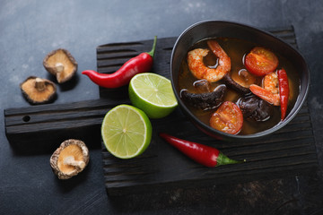 Bowl of Tom Yum soup on a black wooden serving board with some of its cooking components, studio shot