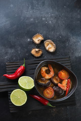 Thai traditional Tom Yum soup on a dark metal background, view from above with space, vertical shot
