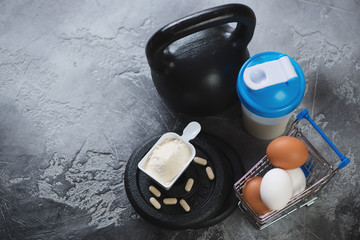 Kettlebell, shaker with protein, weight plates and chicken eggs. Horizontal shot with copyspace on a grey concrete background