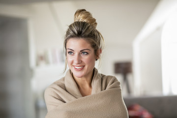 Beautiful young woman in middle age at living room covered with  blanket laughs in the afternoon. Winter time
