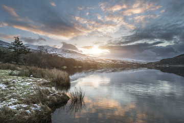 Stunning sunrise landscape image in Winter of Llyn Cwellyn in Snowdonia National Park with snow capped mountains in background