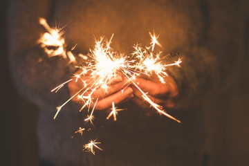 Burning sparkler in a woman hand, new year, christmas holiday concept.