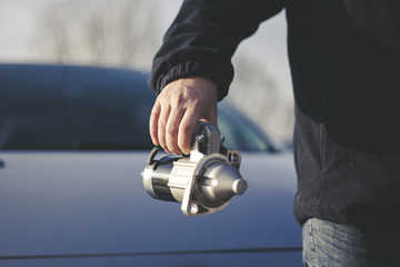 A man hand holding an electric starter with a car in the background, car spare parts.