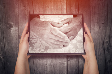 Hands of unrecognizable woman holding elderly woman hands picture. Concept of love and support.