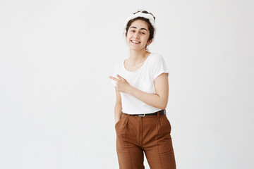 Advertising concept. Indoor shot of cheerful smiling young woman with curly hair in bun pointing index finger at copy space on white blank background
