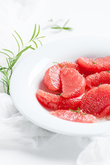 Peeled slices of ripe grapefruit and a branch of fresh rosemary on a white background..
