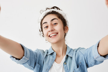 Happy cute girl with dark and wavy hair in bun stretching arms to camera, isolated against white background. Trendy female dressed in denim shirt smiling broadly at camera.
