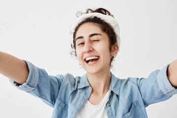 Happiness, joy, youth. Young positive girl dressed in denim shirt over white t-shirt stretching arms, smiling broadly, blinking, having good mood, demonstrating white even teeth