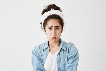 Portrait of miserable gloomy dark-haired female looks offended, frowns face in displeasure, hears unpleasant comments about her work. Young woman in denim shirt abused by colleagues or friends