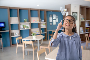 Little asian girl wear eye glass and pointing finger upward in modern class room, Concept of thinking or education