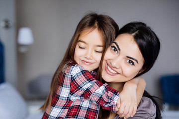 Beautiful young mother and her daughter are hugging and smiling while sitting on the bed at home