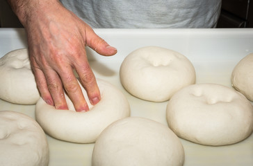 The chef prepares the balls of pizza dough on the floured table.Food, italian cuisine and cooking concept. Preparation of the Italian Pizza