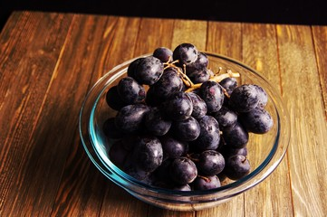 High angle shot of fruit bowl full of violet purple bunch of  grapes on wooden cabinet