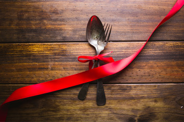 spoon and fork with a red bow on a wood background