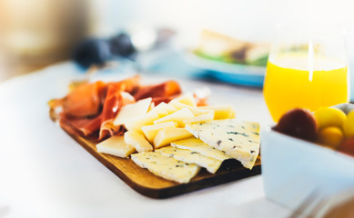 Prosciutto, parmesan on wooden board on kitchen table, blur concept, spanish breakfast with serrano jamon and gorgonzola cheese closeup, traditional food on restaurant or cafe