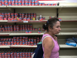 A woman looks for groceries and goods at a supermarket in Caracas