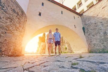 Junges Touristenpaar spaziert durch Torbogen am Innufer in Passau