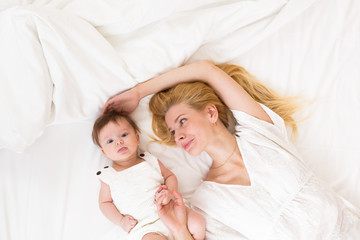 Mother and child on a white bed top view. Mom and baby girl with blue eyes playing in white bedroom. Parent and little kid relaxing at home and having fun together