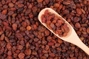 Fresh raisins in a wooden spoon.