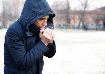 Man dressed in warm clothing in snowy weather