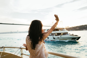 Young girl traveler relaxes during a cruise on a yacht, waving her hand to a passing ship at sunset, a bridge against a background