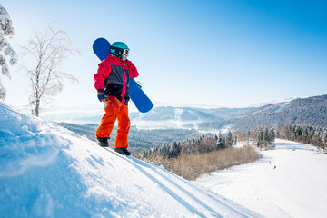 Male snowboarder standing on the snowy slope of the mountain looking away resting after riding in the morning at winter ski resort nature relaxation recreation sports lifestyle active people concept