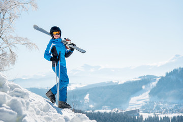 Full length shot of a female skier walking down the slope with her skis on the shoulder, smiling to the camera copyspace winter ski resort, blue sky and mountains on the background