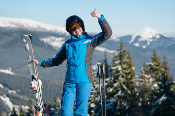 Shot of a happy female wearing skiing gear smiling showing thumbs up posing in the mountains enjoying her vacation at ski resort positivity lifestyle travel trip sports concept