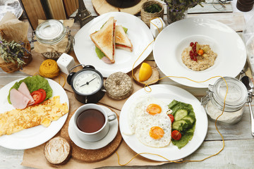 Four breakfast on a wooden table surrounded by various elemeetov on a wooden table