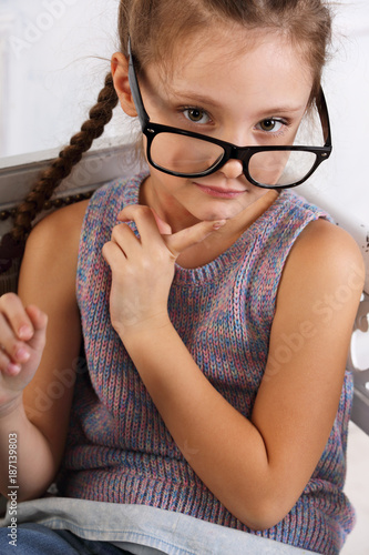 0cb3d4ff45 Happy smiling thinking kid girl in eyeglasses looking and thinking about.  Closeup studio portrait
