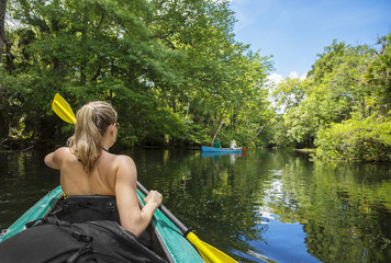 Woman kayaker paddling down a beautiful jungle river with two people in a canoe on a gorgeous day.