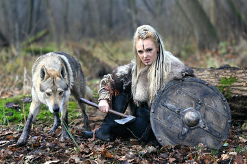 Beautiful viking warrior woman in traditional warrior clothes, with ax and shield, next to an wild wolf, ready to attack