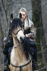 Beautiful viking warrior woman in traditional warrior clothes, with ax and shield, riding a horse in forest