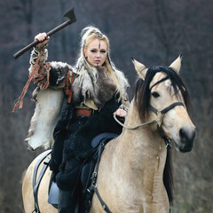 Beautiful viking warrior woman with ax in traditional warrior clothes riding a horse, welcom