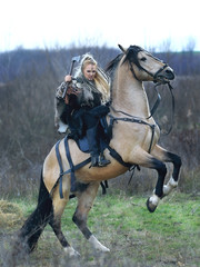 Beautiful viking warrior woman with ax in traditional warrior clothes riding a horse, threatening and ready to battle