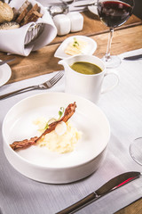 Cream of sorrel and green vegetables soup with quail egg, sour cream, mashed potatoes and crispy bacon served in a jug in a restaurant