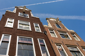 The facade of two historical Dutch houses in Amsterdam.
