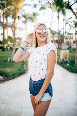 Relaxed happy smile young woman in sunglasses on terrace of hotel on palms background. Summer vocation