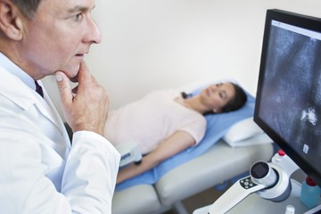 Doctor looking at screen with hand on chin