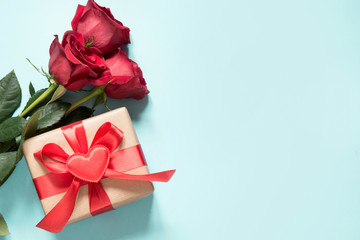 Bouquet of red roses and gift with red ribbon and heart on blue. Valentine's card. Close up. Copy space.