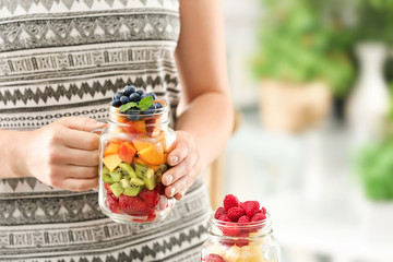 Woman holding mason jar with fruits and berries on blurred background