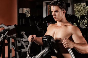 Young man training on exercise machine in gym