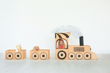 Little girl playing with cardboard train on light wall background