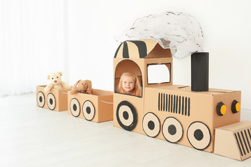 Little girl playing with cardboard train in light room