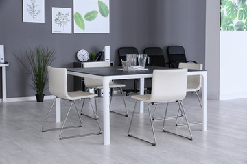 Modern office interior with table and white chairs